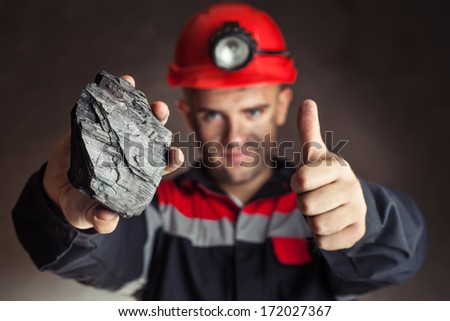 Coal miner showing lump of coal with thumbs up against a dark background - stock photo