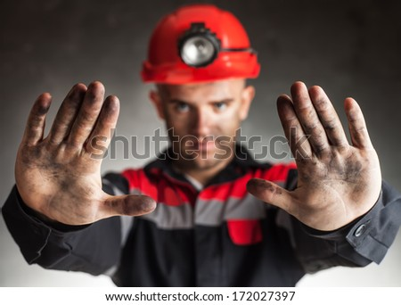 Coal miner with dirty hands making stop gesture warning of danger against a dark background - stock photo