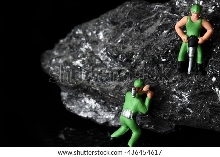 Coal miniature miners / miniature model miners on a piece of coal on a carbon fiber background - stock photo
