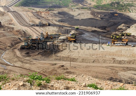 Coal mining in an open pit with huge industrial machine - stock photo