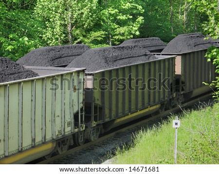 Coal piled in open railroad cars - stock photo