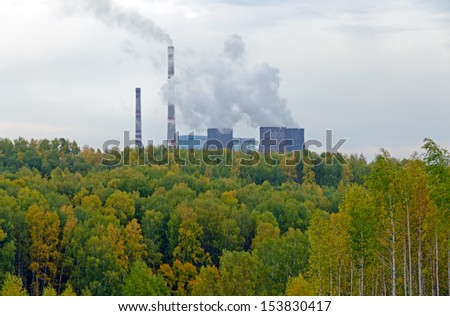 Coal power station behind fall forest - stock photo