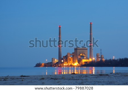 Coal power station by a lake in the evening reflecting in the water - stock photo