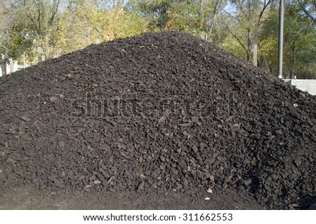 Coal washed and dried in a pile in the warehouse waiting for sale. - stock photo