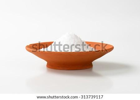 Coarse grained salt in terracotta bowl - stock photo