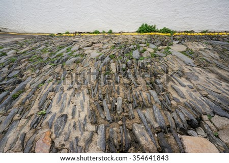 coarse stone pavement against plastered wall as background; all together resembling a landscape with a greenery stripe between ground surface and pale sky - stock photo