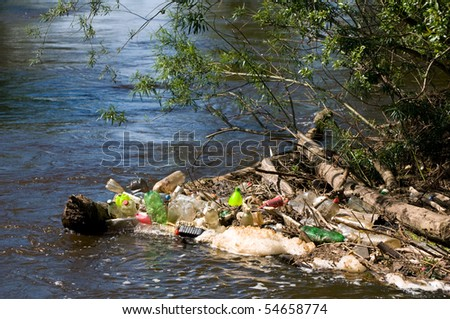 Coast and plastic bottles garbage damage river after flood in Poland. Scatter empty plastic bottles stuck on log in water under small twigs of bush, dump environment, objects spilled out, horizontal. - stock photo