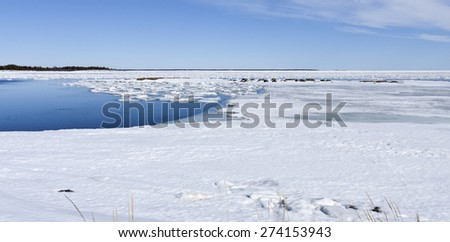 Coast, coastline and shore of the Baltic Sea in March during the day, hours when the ice at sea breaks up. Sunny day by the sea. Lighthouse, beacon in the background. Cliffs, rocks this side. - stock photo