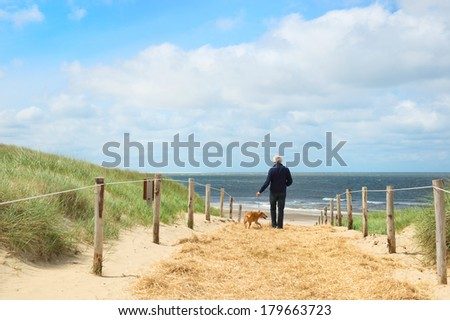 Coast from Northsea at Dutch wadden island Texel with man and dog - stock photo