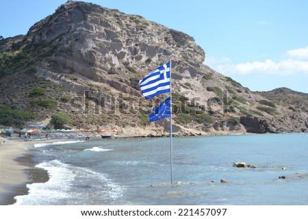 Coast of the Aegean Sea. Flagstaff at sea. Flags of Greece and the European Union - stock photo