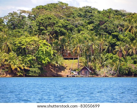 Coast of the Caribbean sea with house surrounded by lush tropical vegetation and cabin over the water, Bocas del Toro, Panama - stock photo