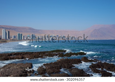 Coastal city of Iquique in northern Chile located between the waters of the Pacific Ocean and sand dunes of the Atacama Desert. - stock photo