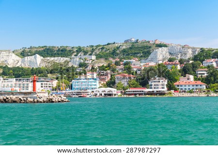 Coastal landscape of Balchik resort town. Entrance to port, red lighthouse on the pier. Coast of the Black Sea, Varna region, Bulgaria - stock photo