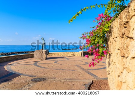 Coastal promenade with flowers and statue in Costa Adeje seaside town, Tenerife, Canary Islands, Spain - stock photo