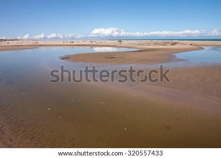 coastal river and tidal lagoon, Pouawa Marine Reserve, Gisborne, East Coast, North Island, New Zealand  - stock photo