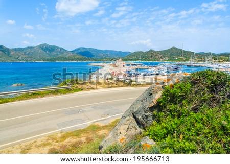 Coastal road along a sea with view of port in Porto Giunco, Sardinia island, Italy - stock photo