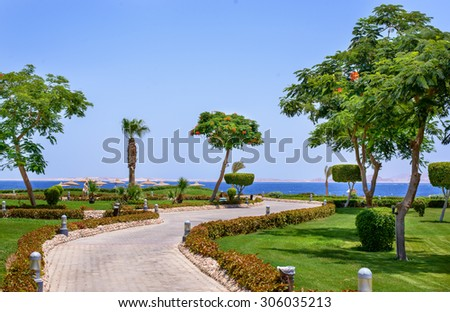 Coastal road on a tropical resort leading through manicured lawns and trees to umbrellas on the beach and a calm blue ocean - stock photo