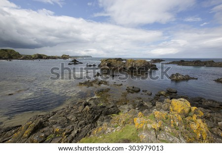 Coastal rocky landscape showing rocky  beaches and cliffs in County Antrim in the UK on the Atlantic north west coast of Ireland on a sunny day with  blue skies with clouds and mountains. - stock photo
