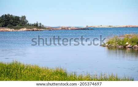Coastal scene from the swedish coastline with small islands in the archipelago and a lighthouse in the center far away - stock photo