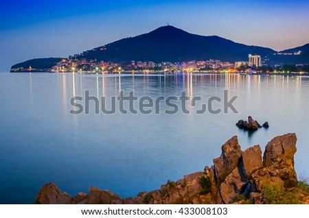 Coastline of illuminated Budva in Montenegro. Landscape of european town near the sea. - stock photo