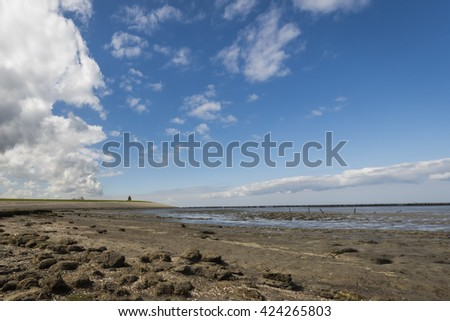Coastline of the Waddensea at Friesland with mud flats and protection poles and dikes. In the background the church of Wierum. - stock photo
