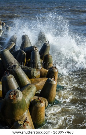 Coastline with concrete wave breaker. - stock photo