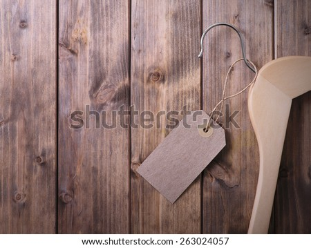 coat hanger with blank tag on background of wooden planks - stock photo