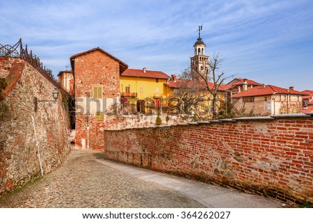 Cobbled street, red brick wall and colorful houses in old town of Saluzzo in Piedmont, Northern Italy. - stock photo