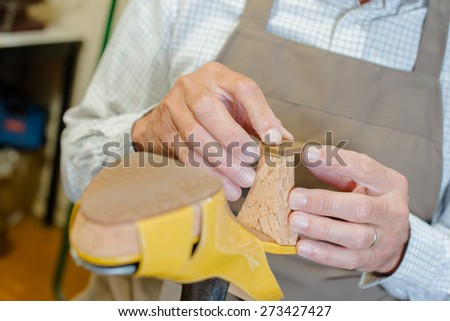 Cobbler working on a shoe heel - stock photo