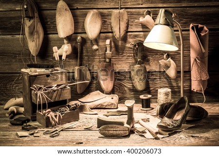 Cobbler workshop with tools, shoes and laces - stock photo