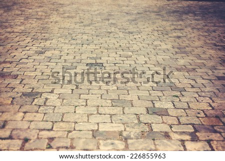 cobbles in an old European city, background and texture, with retro toning - stock photo
