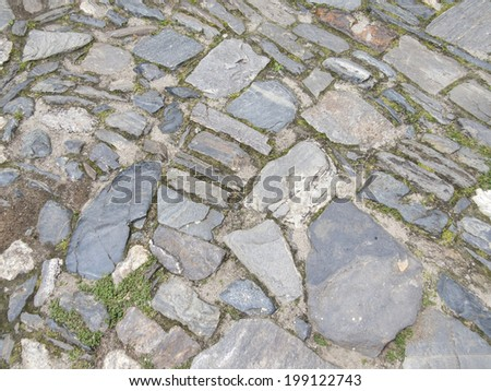 Cobblestone background with natural stones of irregular shape and grass growing between the stones - stock photo