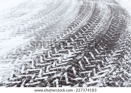Cobblestone pavement in winter time with tire tracks - stock photo