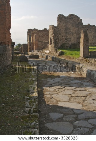 Cobblestone street and ancient ruins of Pompeii, Italy. - stock photo