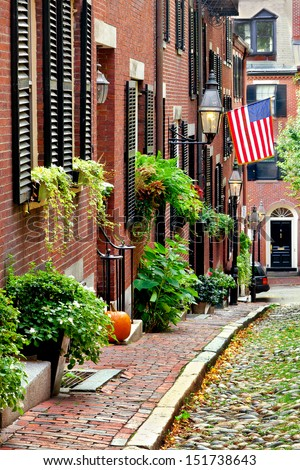 Cobblestone street in Boston. Historic Acorn Street in Beacon Hill, called the most picturesque street in America, with a row of vintage red brick buildings. Vertical - stock photo