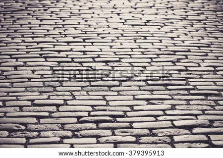 Cobblestones shining during sunset. Toned in black and white - stock photo