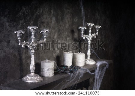 Cobweb Covered Candles and Candelabras on Mantle in Eerie Haunted House Setting - stock photo