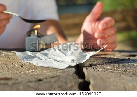 Cocaine addict heating the drug over a flame in a spoon in preparation for shooting up with the syringe, close up of hands at outdoor table - stock photo