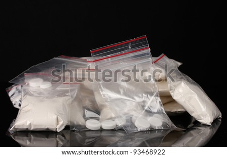 Cocaine and drugs in packages on black background - stock photo