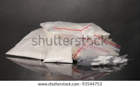 Cocaine and drugs in packages on grey background - stock photo