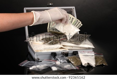 Cocaine and marijuana in a suitcase wiht hand holding a package of cocaine isolated on white - stock photo