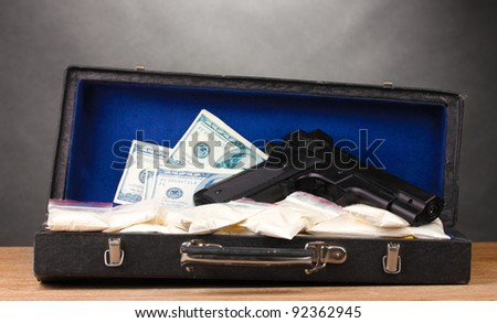 Cocaine, dollars and handgun in case on wooden table on grey background - stock photo
