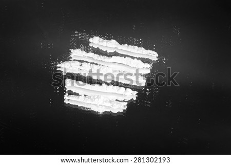 Cocaine powder in lines on a grunge black background - stock photo