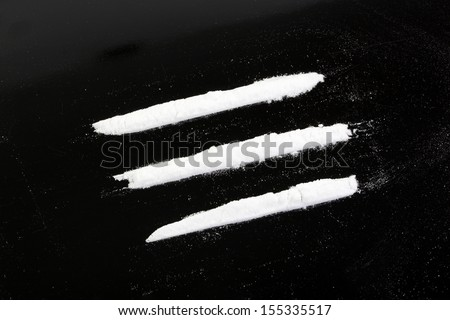 cocaine powder in three lines on a black background - stock photo