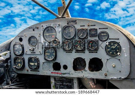 Cockpit of old airplane on blue sky background - stock photo