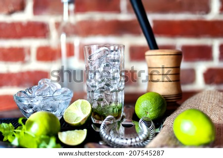 cocktail at bar, fresh alcoholic drink with limes and ice - stock photo