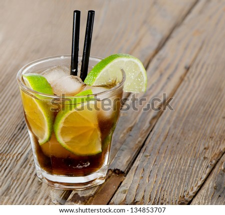 Cocktail Cuba Libre on a wooden table - stock photo