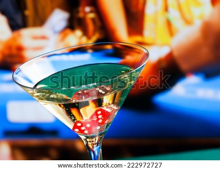 cocktail glass in front of gambling table, casino concept - stock photo
