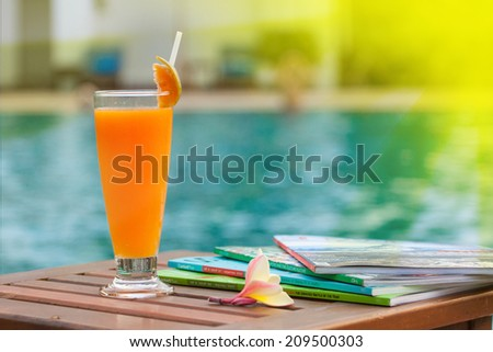 Cocktail glass near swimming pool - stock photo
