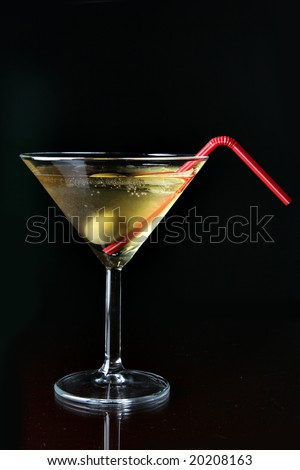 Cocktail glass with ice and olive close-up over black background - stock photo